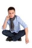 Hombre pensativo que se sienta con las piernas cruzadas Fotos de archivo libres de regalías