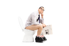 Hombre pensativo que se sienta en retrete y que sostiene un papel Imagenes de archivo