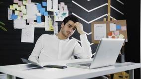 Hombre pensativo que se sienta en un escritorio y un pensamiento almacen de video