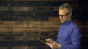 Hombre pensativo que usa el dispositivo de la tableta almacen de video