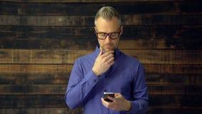 Hombre pensativo que usa el dispositivo del teléfono almacen de metraje de vídeo