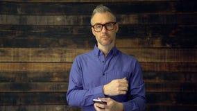 Hombre pensativo que usa el dispositivo y las miradas del teléfono serios almacen de metraje de vídeo