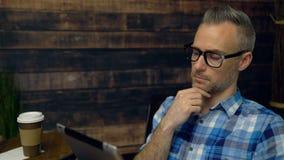 Hombre pensativo que usa la tableta en café metrajes