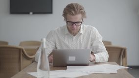 Hombre pensativo rubio acertado hermoso del retrato en los vidrios que se sientan en la tabla en una oficina cómoda ligera en fre metrajes