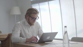 Hombre pensativo rubio confiado en los vidrios que se sientan en la tabla en una oficina cómoda ligera delante del netbook almacen de video