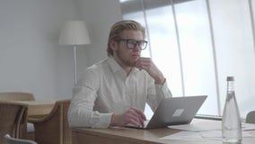 Hombre pensativo rubio en los vidrios que se sientan en la tabla en una oficina c?moda ligera delante del netbook hermoso metrajes