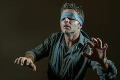 Hombre perdido y confuso joven vendado los ojos de con la corbata que juega desafío viral peligroso de la tendencia de Internet c fotos de archivo libres de regalías
