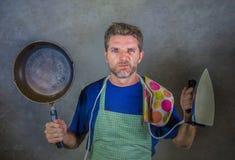 Hombre perezoso subrayado y abrumado atractivo joven que sostiene la cacerola y el hierro de la cocina en la tensión y la expresi foto de archivo libre de regalías
