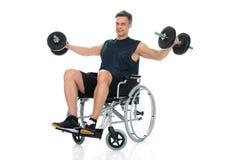 Hombre perjudicado en la silla de ruedas que se resuelve con pesa de gimnasia Fotografía de archivo