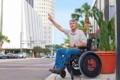 Hombre perjudicado en una silla de ruedas que graniza un taxi en la ciudad Imagen de archivo libre de regalías