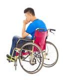 Hombre perjudicado que se sienta en una silla de ruedas y un pensamiento Foto de archivo libre de regalías