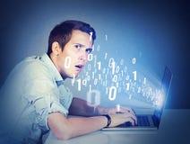 Hombre perplejo con el aprendizaje del ordenador portátil de informática imagen de archivo