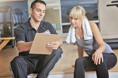 Hombre personal del instructor de la mujer del gimnasio con el equipo de entrenamiento del peso imagen de archivo libre de regalías