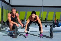 Hombre personal del instructor del gimnasio con la mujer de la barra del levantamiento de pesas Foto de archivo
