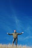 Hombre positivo en un fondo del cielo azul Foto de archivo libre de regalías