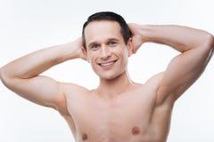 Hombre positivo feliz que lleva a cabo sus manos detrás de la cabeza Foto de archivo