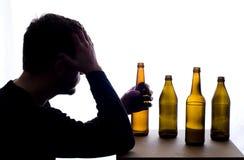 Hombre preocupado con las botellas de cerveza Fotos de archivo