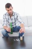Hombre preocupado con una cerveza y su medicina puesta Imágenes de archivo libres de regalías