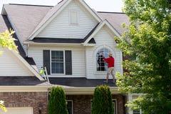 Hombre preocupado por su casa que limpia las ventanas del piso superior foto de archivo