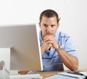 Hombre preocupante en las cuentas que pagan del escritorio y del ordenador Imagen de archivo