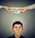 Hombre preocupante que mira para arriba las manos que intercambian el dinero Imagen de archivo libre de regalías