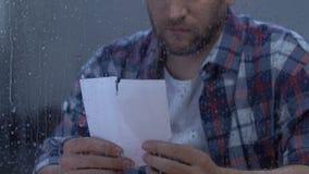 Hombre presionado que mira la foto rasgada, desintegración dolorosa sufridora, soledad almacen de metraje de vídeo