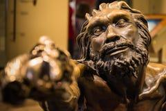Hombre primitivo que lleva a cabo la característica H de la instalación del bronce de la estatua del palillo fotos de archivo libres de regalías