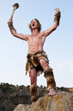Hombre primitivo que se coloca en una roca Imagenes de archivo