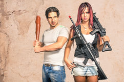 Hombre primitivo y mujer moderna con las armas - pares divertidos Fotos de archivo