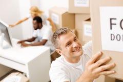 Hombre productivo encantador que mueve las cajas con las fuentes Fotos de archivo