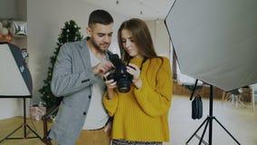 Hombre profesional del fotógrafo que muestra las fotos en la cámara digital a la muchacha modelo hermosa en estudio de la foto de fotos de archivo