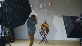 Hombre profesional del fotógrafo que toma la foto de la muchacha modelo hermosa con la cámara digital en estudio imagen de archivo libre de regalías