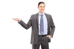 Hombre profesional joven en un traje que gesticula con su mano Foto de archivo