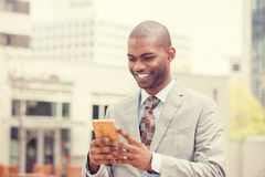 Hombre profesional urbano sonriente feliz joven que usa el teléfono elegante al aire libre fotos de archivo libres de regalías