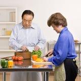 Hombre provechoso que prepara la ensalada con la esposa en cocina imagenes de archivo