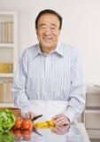 Hombre provechoso que prepara la ensalada en cocina fotografía de archivo