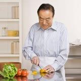 Hombre provechoso que prepara la ensalada en la cocina para la cena fotografía de archivo