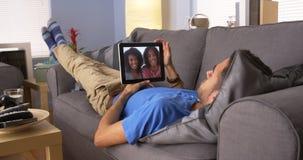 Hombre puertorriqueño que habla con los amigos en la tableta Fotografía de archivo libre de regalías