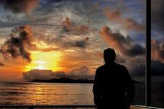 Hombre, puesta del sol sobre el mar y isla   Fotografía de archivo