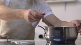 Hombre que añade el paprika cosechado en la cacerola y el revolvimiento, cocinando el guisado vegetal almacen de metraje de vídeo