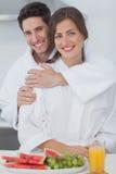 Hombre que abraza a su esposa en la cocina Fotos de archivo