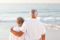 Hombre que abraza a su esposa en la playa Fotografía de archivo