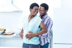 Hombre que abraza a su esposa mientras que se coloca Imagenes de archivo