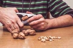 Hombre que abre algunas nueces en una tabla Fotos de archivo libres de regalías