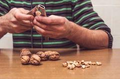 Hombre que abre algunas nueces en una tabla Imágenes de archivo libres de regalías