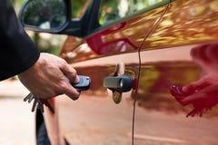 Hombre que abre la puerta de coche con teledirigido Imagen de archivo libre de regalías