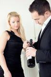 Hombre que abre una botella de vino rojo fotografía de archivo