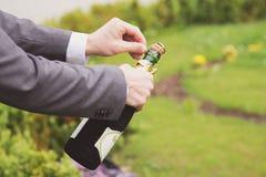Hombre que abre una botella del champán Imagen de archivo