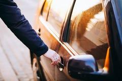 Hombre que abre una puerta de coche Mano en la manija Foto de archivo libre de regalías