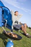 Hombre que acampa al aire libre y que cocina Fotos de archivo libres de regalías
